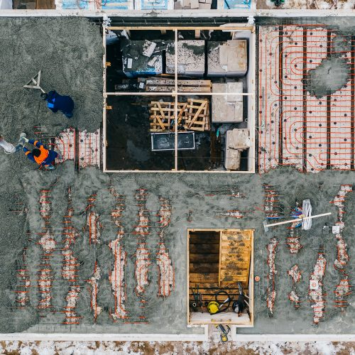 aerial-view-of-construction-workers-pouring-a-wet--R3LHVRB